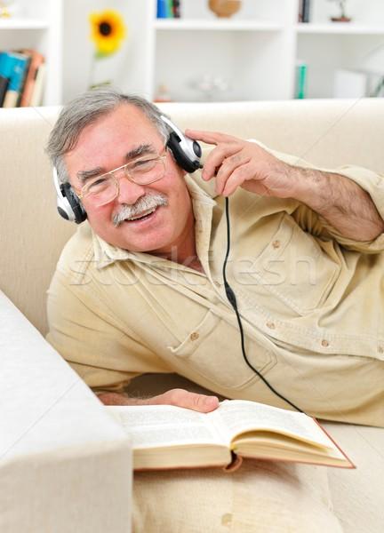 Happy senior man listening to music Stock photo © erierika