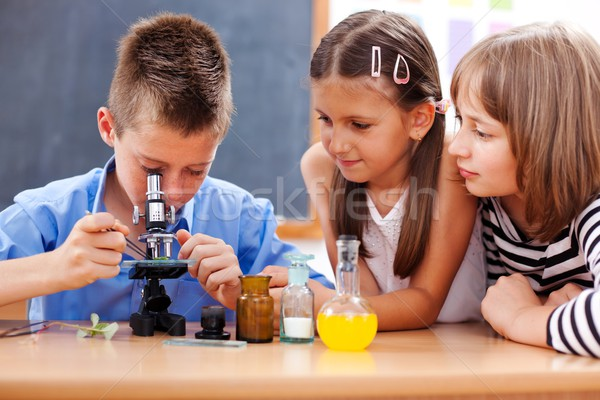 Boy looking into microscope Stock photo © erierika