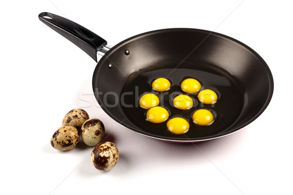 Whole and broken quail eggs in pan Stock photo © erierika