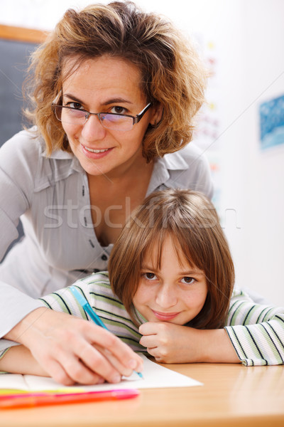 Teacher helping schoolgirl writing Stock photo © erierika