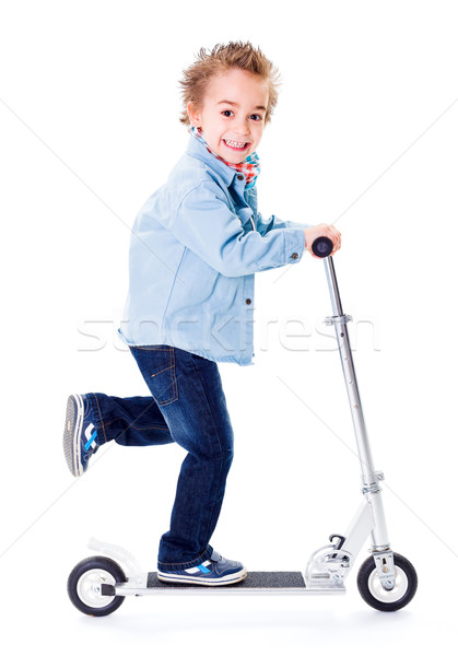 Cheerful boy going fast with scooter Stock photo © erierika