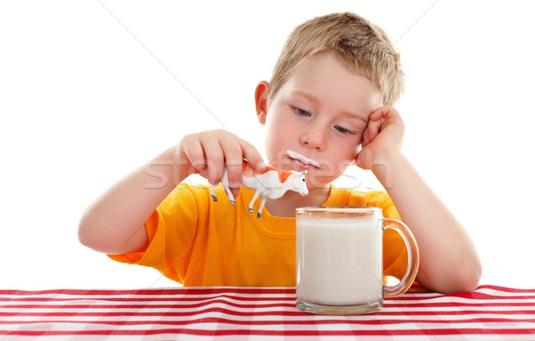 Young kid playing with toy cow behind glass of milk Stock photo © erierika