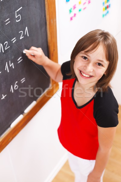 Schoolgirl looking up in front of chalkboard Stock photo © erierika