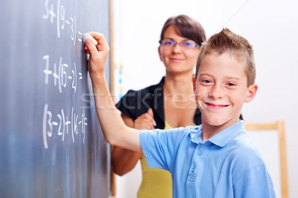 Boy standing on chalkboard in front of teacher Stock photo © erierika