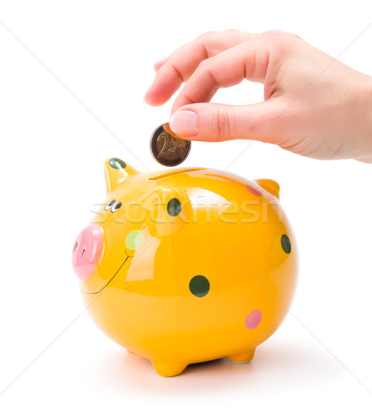 Hand putting a coin into piggy-bank Stock photo © erierika