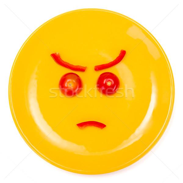 Enojado cara sonriente placa amarillo tomate pimienta Foto stock © erierika