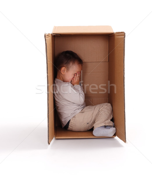 Sad little boy hiding in cardboard box Stock photo © erierika