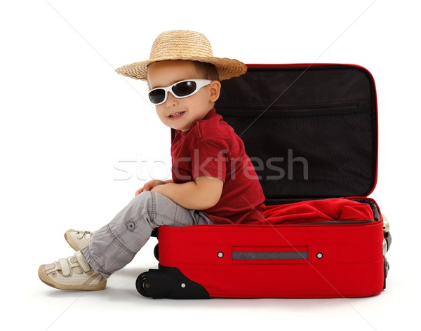 Confident little boy wearing straw hat, sitting in suitcase Stock photo © erierika