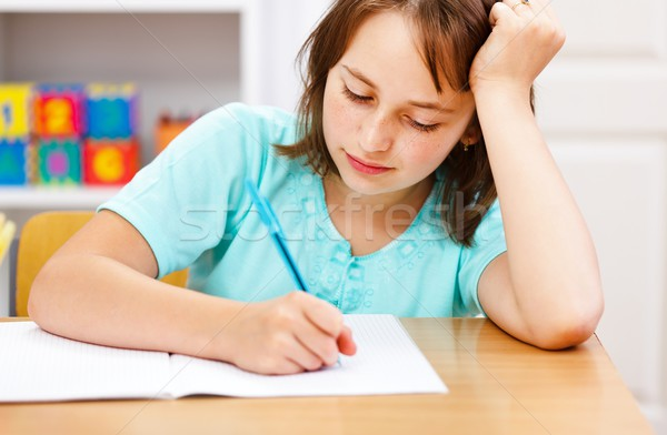 Schoolgirl writing boring homework Stock photo © erierika