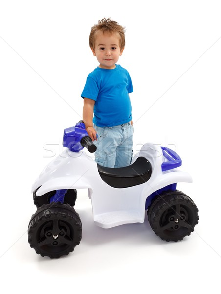 Stock photo: Little boy standing near toy off road quad