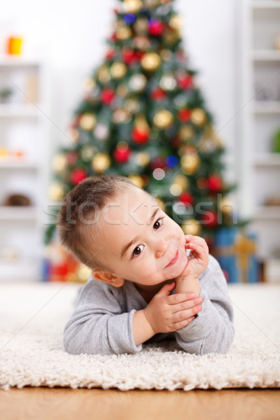 Cute boy laying in front of christmas tree Stock photo © erierika