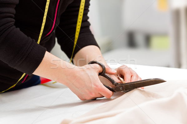 Dressmaker cutting fabric with scissors Stock photo © erierika