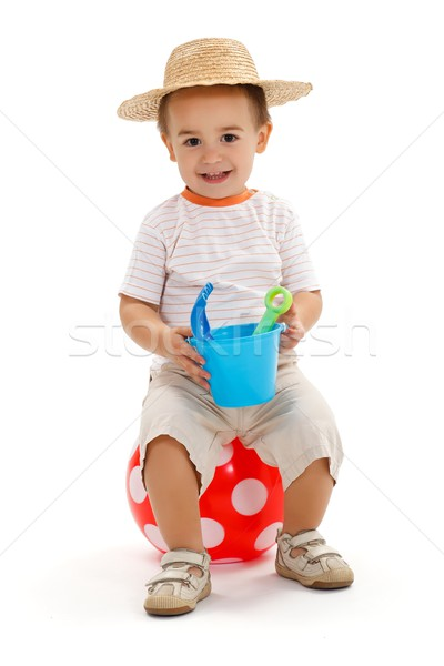 Little boy sitting on dotted ball, holding sandbox toys Stock photo © erierika