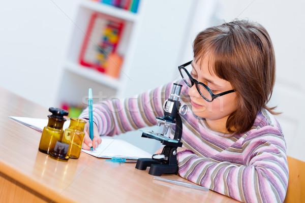 Teen science girl with microscope Stock photo © erierika