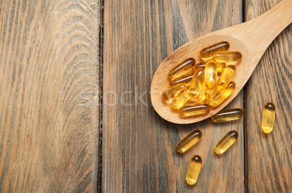 Halolaj kapszulák kanál fából készült étel hal Stock fotó © Es75