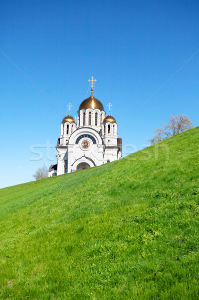 White Orthodox Church with golden shining domes on green hill Stock photo © Escander81