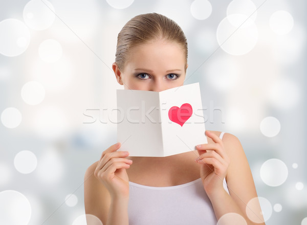 beautiful young woman holding a valentine postcard Stock photo © evgenyatamanenko