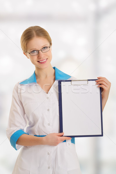 Smiling young female medical doctor with clipboard Stock photo © evgenyatamanenko