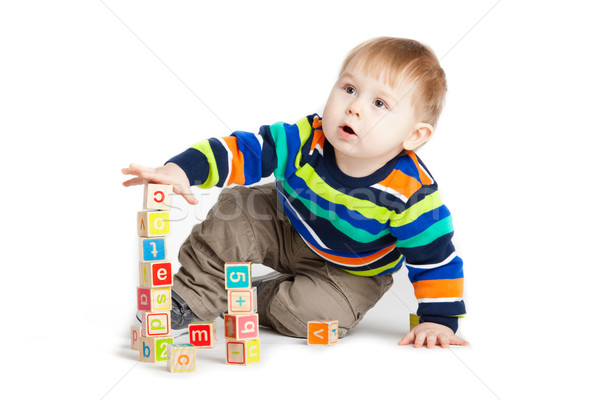 Stock photo: baby playing with wooden toy cubes with letters. Wooden alphabet