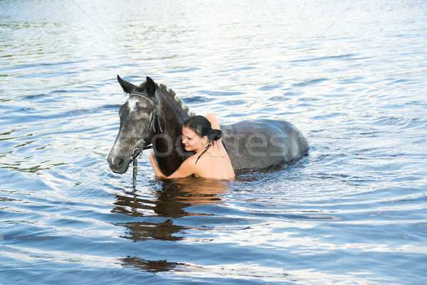 woman swimming winth her black stallion in river Stock photo © fanfo