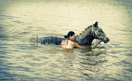 woman swimming winth her black stallion Stock photo © fanfo