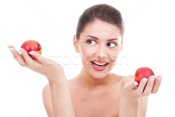 Stock photo:  Young woman deciding on apples