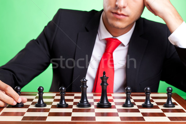 Stock photo: business man standing in front of chess line-up