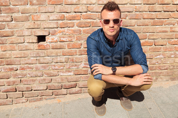 casual man sits with hands folded Stock photo © feedough