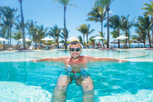 Feliz homem relaxante infinito piscina praia Foto stock © feedough