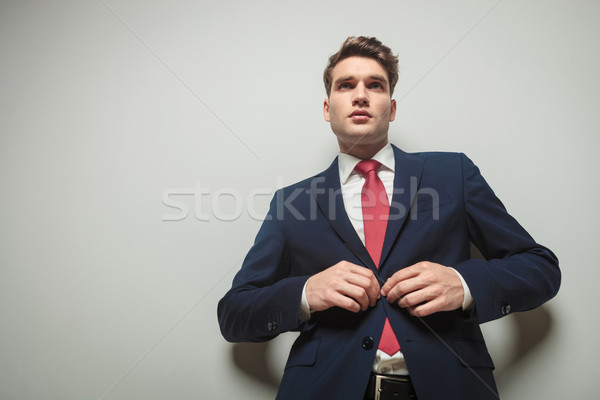 Young attractive business man closing his jacket  Stock photo © feedough