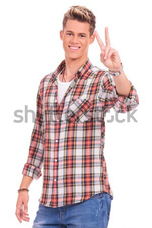 Stock photo: Young man on the phone shows peace sign