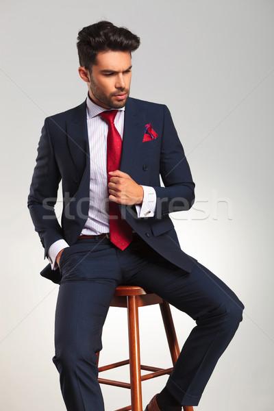 Elegáns üzletember tart kabát ül oldalnézet Stock fotó © feedough