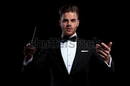 cool elegant young man in tuxedo unbuttoning his coat  Stock photo © feedough
