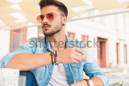 smiling handsome man sitting on street near a lighting pole Stock photo © feedough