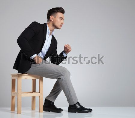 young elegant man is sitting and looking down  Stock photo © feedough