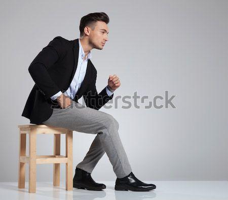 Giovani elegante uomo seduta guardando verso il basso grigio Foto d'archivio © feedough