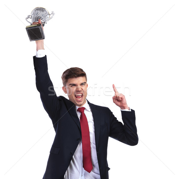 champion businessman holding trophy and pointing finger up Stock photo © feedough