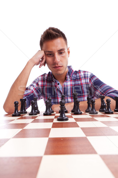 Young casual man thinking in front of the chessboard Stock photo © feedough