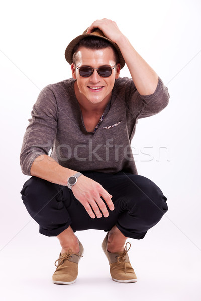 crouched man taking hat off Stock photo © feedough