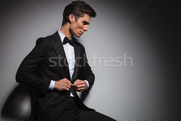 side view of  seated man in tuxedo buttoning his coat Stock photo © feedough