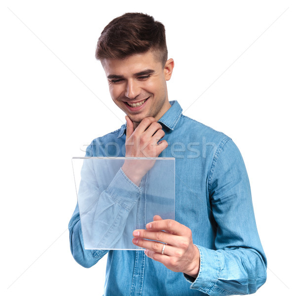 young casual man reading on a transparent futuristic ebook table Stock photo © feedough