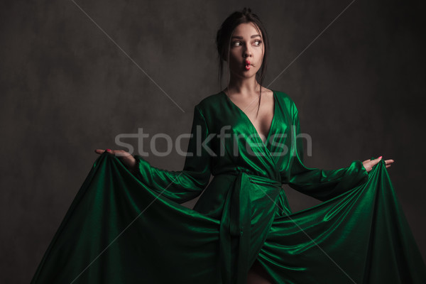curious woman holding her green dress and making a grimace Stock photo © feedough