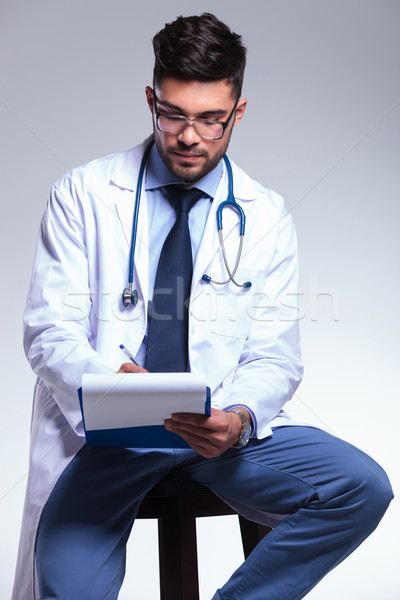 young doctor sitting and writing Stock photo © feedough
