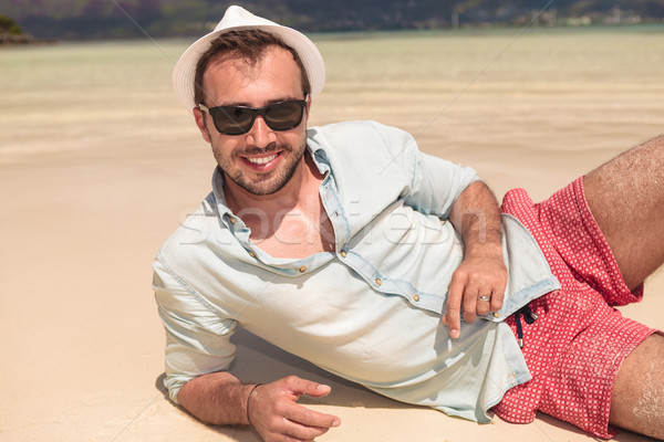 man with hat and sunglasses lying down on the beach Stock photo © feedough