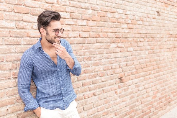smiling casual man near brick wall wondering about something Stock photo © feedough