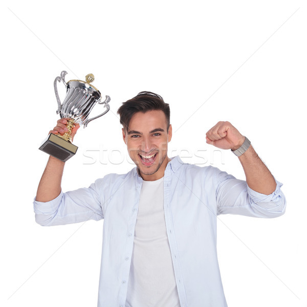 excited young casual man with trophy cup award is celebrating  Stock photo © feedough