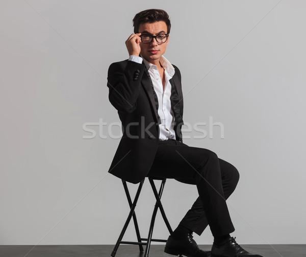 elegant man in tuxedo and undone bowtie fixing his glasses Stock photo © feedough
