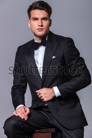 confident businessman dressed in black tuxedo sits on wooden cha Stock photo © feedough