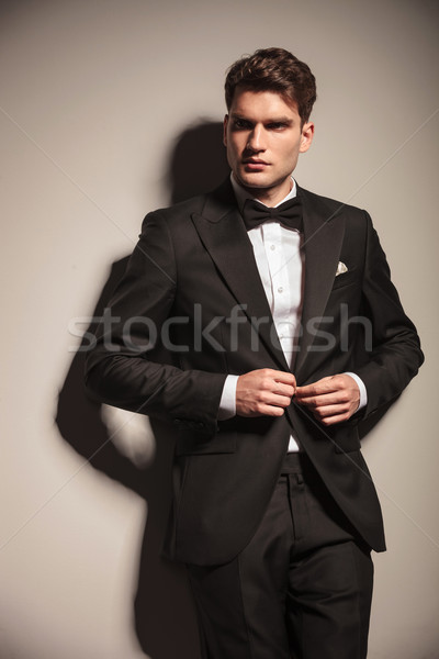 Young handsome business man closing his jacket Stock photo © feedough
