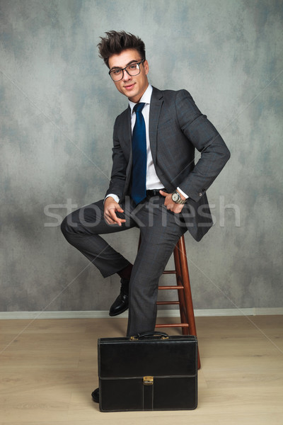 happy young business man sitting near brief case  Stock photo © feedough